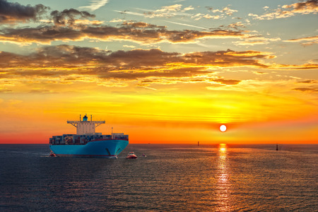 Container ship on sea road during sunrise. Stock Photo