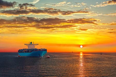 Porte-conteneurs sur la route de la mer au lever du soleil.
