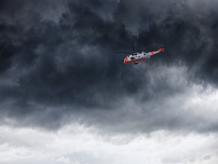 rescue helicopter: Helicopter in Norway seen from below in front dramatic sky.