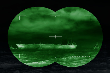 nightvision: Sea freight and contemporary threat of terrorism - Concept Photo. Stock Photo