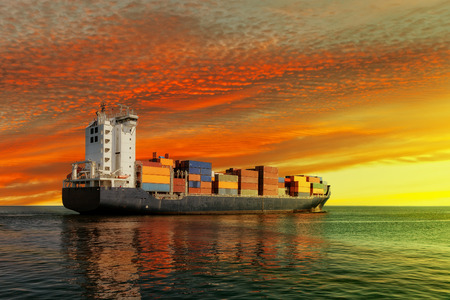 Container ship at sunset in the sea. Stock Photo