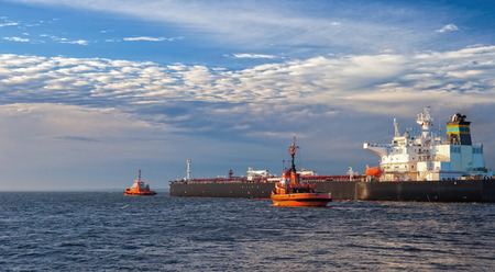 escorting: Tanker ship with escorting tugs leaving port.