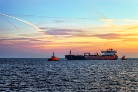 escorting: Tanker ship with escorting tugs on sea at sunrise.