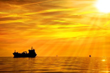 camión cisterna: Buque de carga en el mar en los rayos del sol poniente.