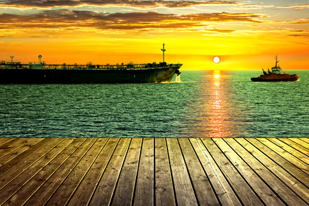 nautical: Tanker ship towed by tugboat. View from wooden pier.