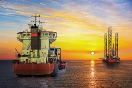 Tanker schip en Oil Platform op offshore gebied bij zonsondergang.