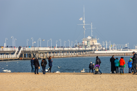 Beach scene of many people walk on the shore in Valentines Day and wooden pier in the distance, on February 14, 2015 in Sopot, Poland.