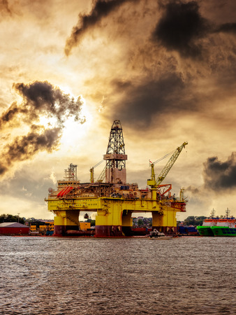 sea shore: Oil rig moored in the harbor against a dramatic sky.