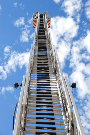 Fire truck ladder leading up into blue sky. photo