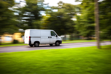 White delivery van speeding on road with blurred countryside panorama in background.