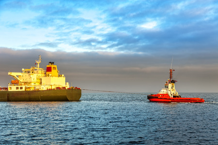 escorting: Tugboat pulling the tanker at sea in the morning.