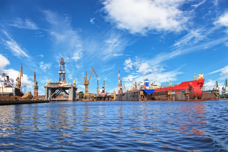 Ships on dock and oil rig in shipyard of Gdansk, Poland.