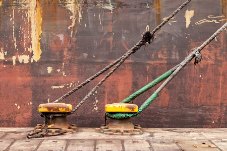 Iron pole for mooring of ships at industrial pier.