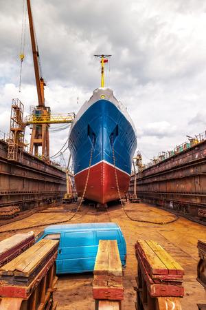 Groot schip op droogdok met zijn bolle delen en ankerketting.