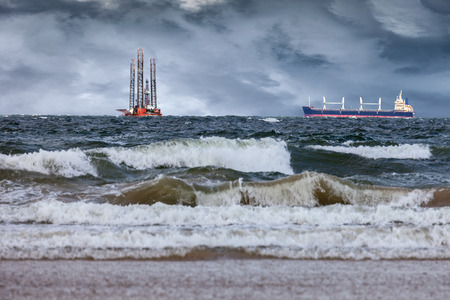 winter storm: Oil Rig with ship at sea during a storm. Stock Photo