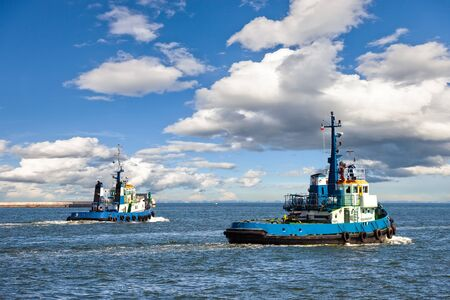 marine industry: Two Tugs Heading out to Sea in Gdynia Poland. Stock Photo