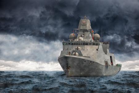 De militaire schip op zee tegen zware wolken. Redactioneel