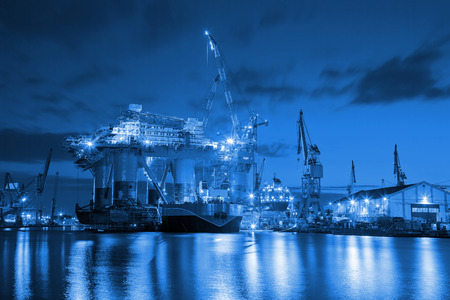 Oil Rig at night in Shipyard industry concept. Stock Photo