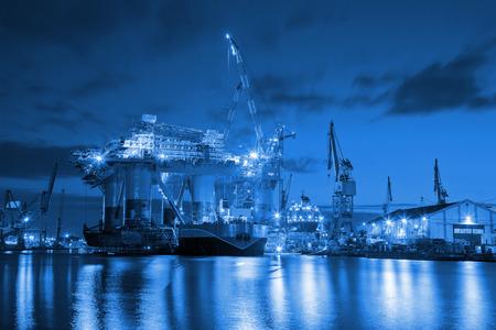 torres petroleras: Plataforma petrolera en la noche en concepto de la industria Astillero.