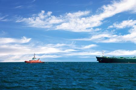 tug boat: Tug boat towing a tanker ship at sea.