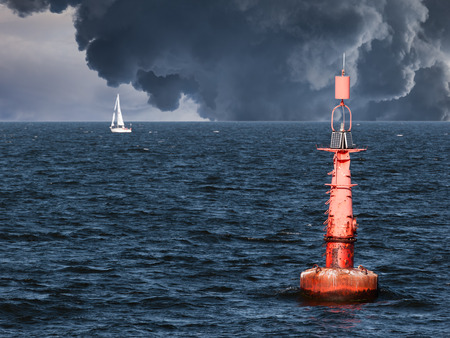 Red buoy on water in a stormy day.