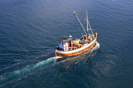 sea fishing: Old wooden fishing boat trawler on sea. Stock Photo