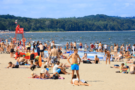 suntanning: Sandy beach scene of many people suntanning, relaxing and enjoying the shore in summer day on August 9, 2015 in Sopot, Poland.