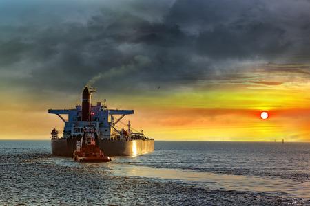 carga: Buque cisterna en el mar en los rayos del sol poniente.