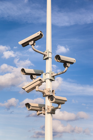 business security: Pole with different security cameras a blue sky.