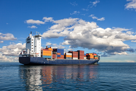 container port: Container ship sailing in to the sea. Stock Photo