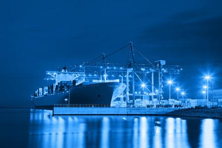 szállítás: Konténerszállító hajó a kikötőben éjszaka - Szállítás koncepció.