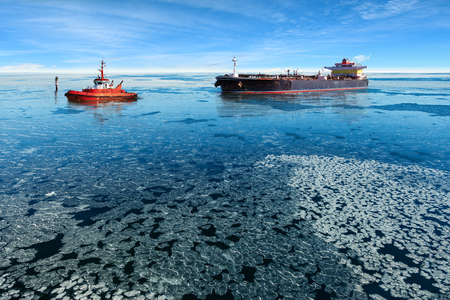 towing: Red tugboat towing a tanker ship at winter. Stock Photo
