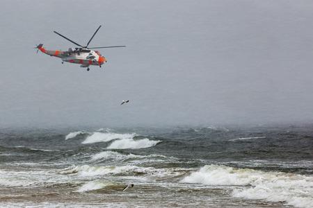 바다에서 어려운 폭풍우에서 헬기 구조 임무.