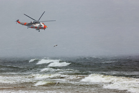 stormy sea: A helicopter rescue mission in difficult stormy weather at sea.