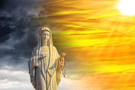 virgen maria: Una estatua de la Virgen María contra un cielo dramático.
