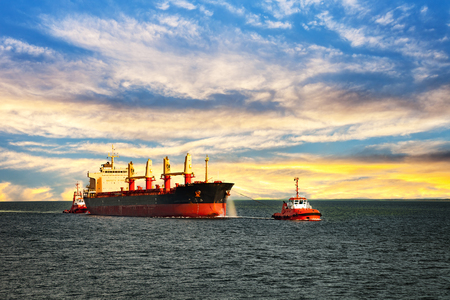 Sleepboten assisteren vrachtschip zee in de ochtend. Stockfoto