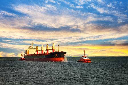 tug boat: Tugboats assisting cargo ship sea in the morning.