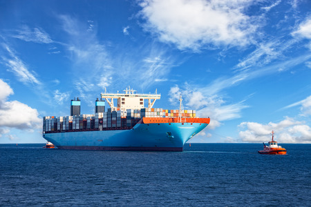 Holowniki wspomagające kontenerowiec ładunku do portu.
