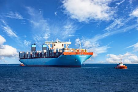 Rimorchiatori assistere container nave da carico al porto.
