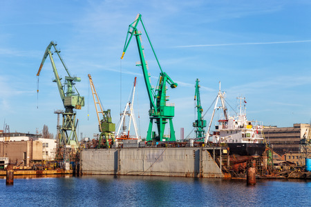 slipway: A view of a large ship under repair in dry dock at a shipyard. Stock Photo