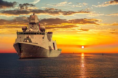 guard ship: The military ship on sea at sunrise. Stock Photo