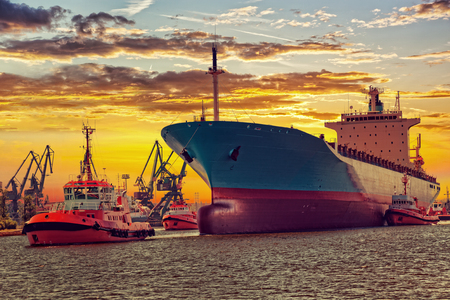 escorting: Big ship with escorting tugs leaving port at sunset Stock Photo