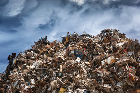 Scrap metal ready for recycling over dark clouds
