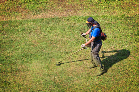 trimmer: Worker mowing grass with trimmer mower