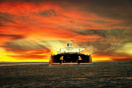 Öltanker Schiff auf hoher See auf dem Hintergrund der Sonnenuntergang Himmel.