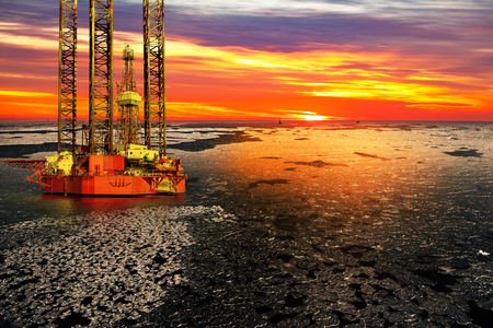 oil and gas: Offshore oil and rig platform in sunrise on frozen sea. Stock Photo