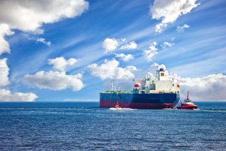 Tanker schip met het begeleiden sleepboten verlaten van de haven.