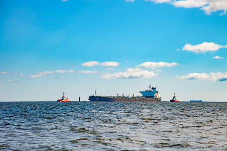 escorting: Tanker ship and tugboats moving in the sea.
