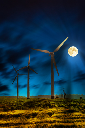energia renovable: Eco power in wind turbine farm at night.