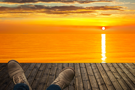 lying forward: Lying on the pier stretching legs in boots and admiring sunrise over sea. Stock Photo